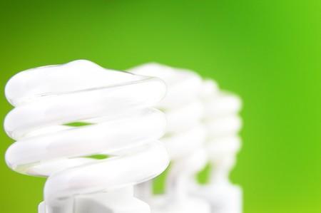 three compact fluorescent light bulbs on green background