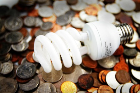 compact fluorescent light bulb on U.S. coins 스톡 콘텐츠