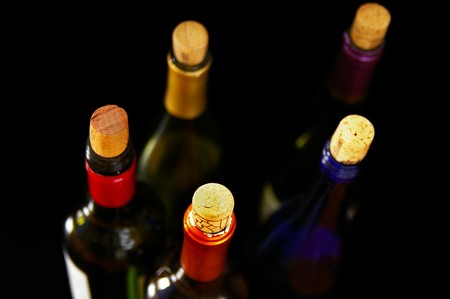 assorted wine bottles and corks on dark background photo