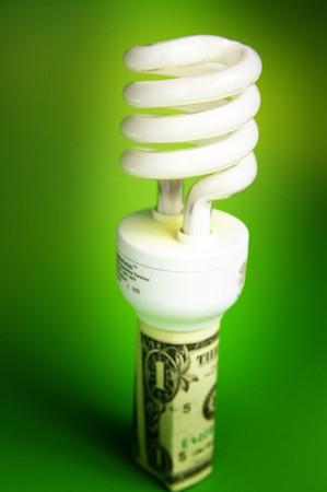Compact fluorescent light bulb, in a dollar bill Stock Photo
