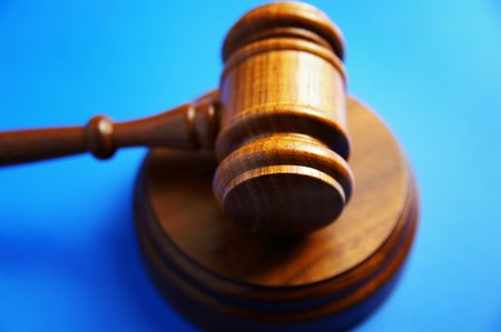 arbitrater: wooden judges gavel on blue background Stock Photo