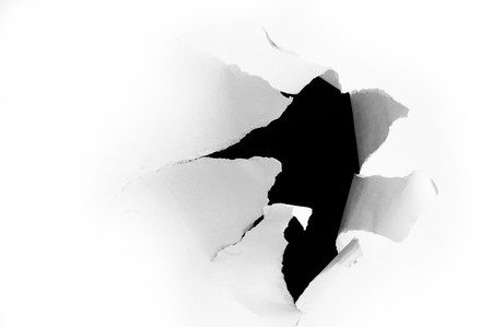 forceful: Side view of a torn jagged hole in paper