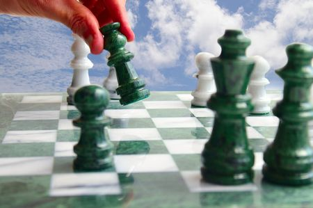 beat the competition: Chess player moving a piece, against blue sky