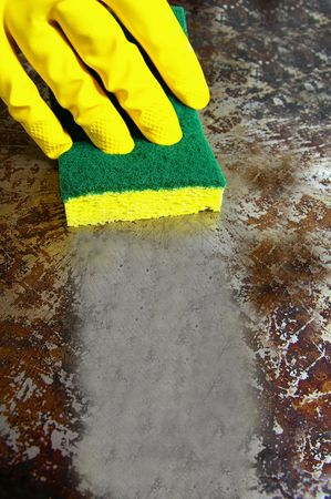 grease: sponge wiping a dirty metal surface clean