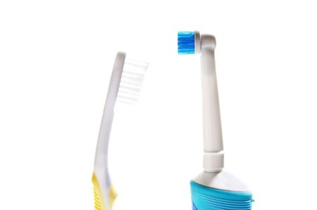 regular and electric tooth brushes on white background