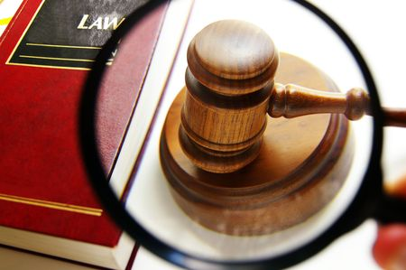 arbitration: magnifying glass examining a judges court gavel, with law book
