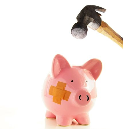 healthcare costs: Piggy bank with bandage about to be smashed by a hammer, metaphor for healthcare costs
