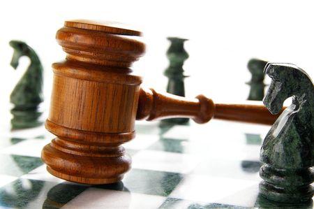 abogado: martillo de ley sobre un tablero de ajedrez con piezas de