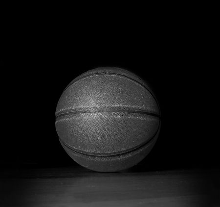 Basketball on the gym floor, on black Stock Photo