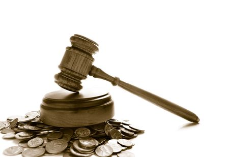 financial official: judges law gavel on a pile of coins, over white