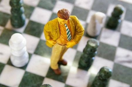 business man figure standing on a chess board Stock Photo - 6173972