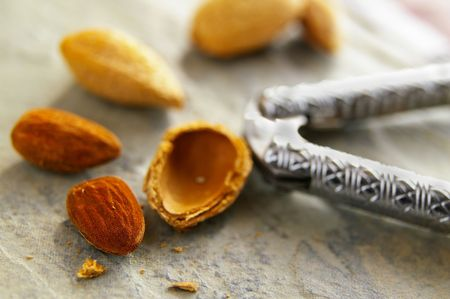 closeup of almond nuts and shells, with nut cracker Stok Fotoğraf