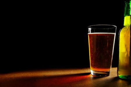 pint glass of beer and bottle, oin black background
