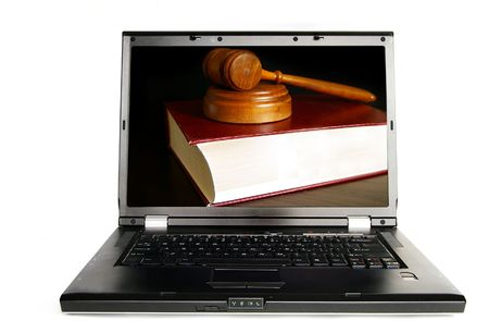 Laptop on white with a lawbook and court gavel photo