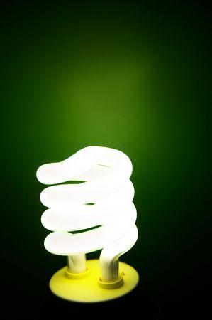 Compact Fluorescent efficient light bulb on green