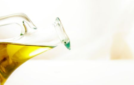 Olive oil in a glass container, tilted to pour