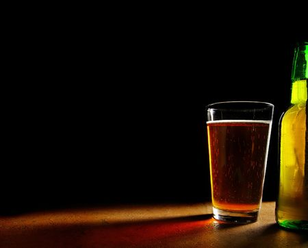 pint glass of beer and bottle, on black background Imagens