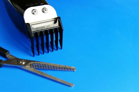 trimmers: barber electric clippers and scissors on blue