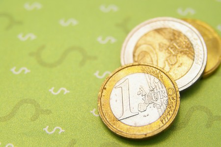 Assorted Euro coins on top of dollar sign Фото со стока