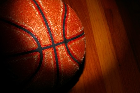 a basketball on the gym floor with dramatic light Stock Photo