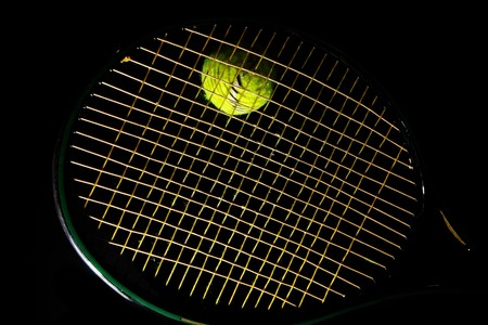 tennis racket and ball on black background
