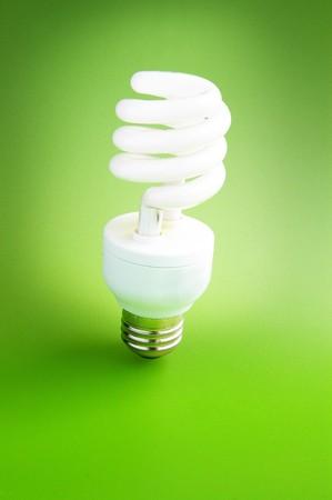 Fluorescent light bulb standing on green background (green power) Stock Photo - 7290813