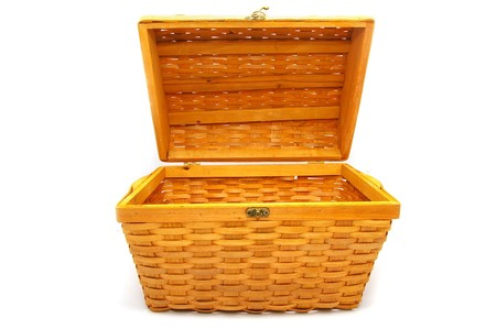 a brown wicker basket, with lid open, on white
