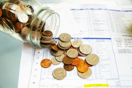 premiums: coin jar with money on medical bills