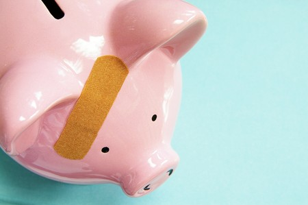 healthcare costs: pink piggy bank with a bandage (healthcare costs)