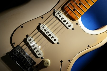 closeup of an electric guitar, on blue
