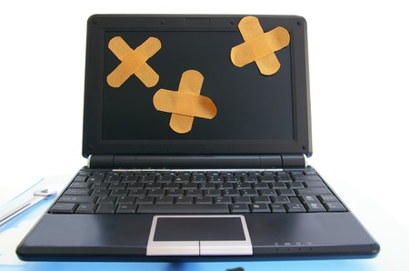laptop computer with bandages - computer repair, or online healthcare concept photo