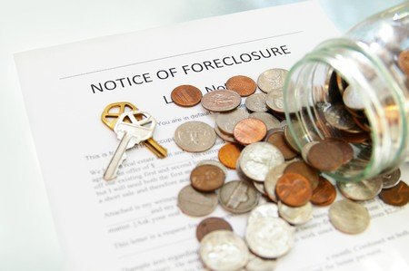 homeownership: bank foreclosure notice and spilled coin jar