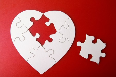 white puzzle heart shape with missing piece, on red photo