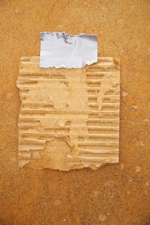 taped: piece of old cardboard taped to a grunge wall