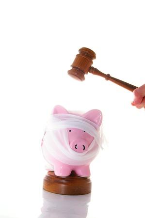bandaged piggy bank with legal gavel photo