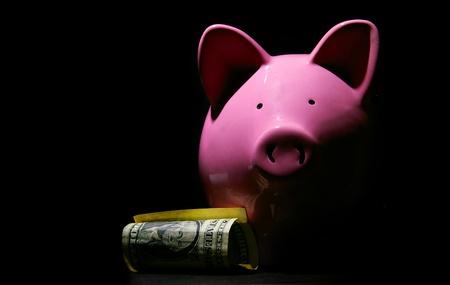 piggy bank and U.S. dollar, on black
