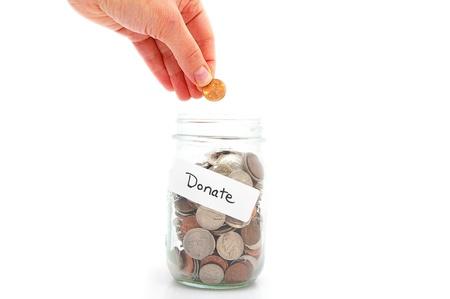 generosit�: mano mettendo un centesimo in un barattolo di denaro - donazione di carit�