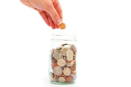 generosit�: mano mettendo penny in un barattolo di moneta, risparmio di denaro Archivio Fotografico