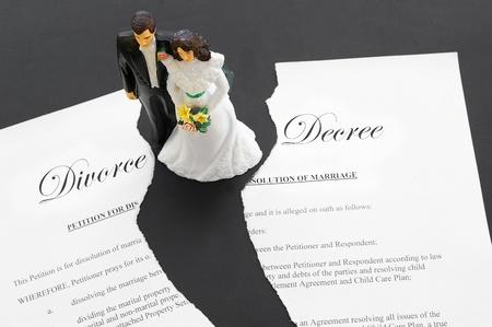 contratos: par de boda topper pastel sobre un documento de divorcio roto Foto de archivo