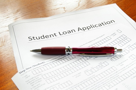 education loan: a blank student loan application, and pen