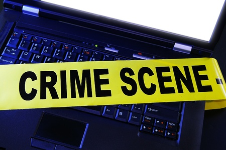 crime: laptop with yellow crime scene tape across it