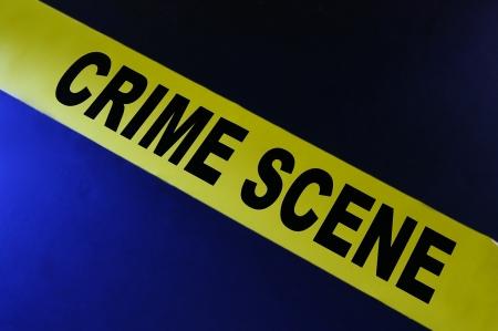 escena del crimen: Cinta de escena de crimen amarillo sobre fondo azul Foto de archivo