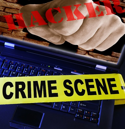 laptop  with yellow crime scene tape across and hacker fist photo