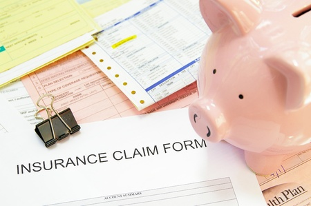 health insurance: Assorted medical bills and a claim form, with piggy bank