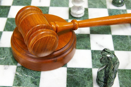 Legal gavel on a chess board with game pieces Stok Fotoğraf