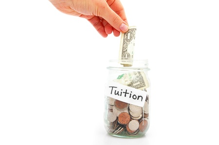 tuition: hand putting a dollar into a jar - education saving
