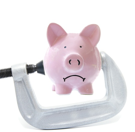 budget crisis: Sad piggy bank being squeezed in a vice, on white