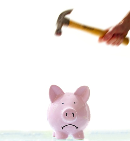 frowning piggy bank about to be smashed by a hammer