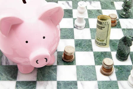 piggy bank with coins and chess pieces photo