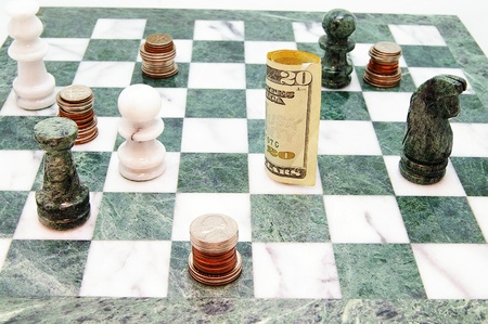 savings risk: coins and money on a chess board Stock Photo